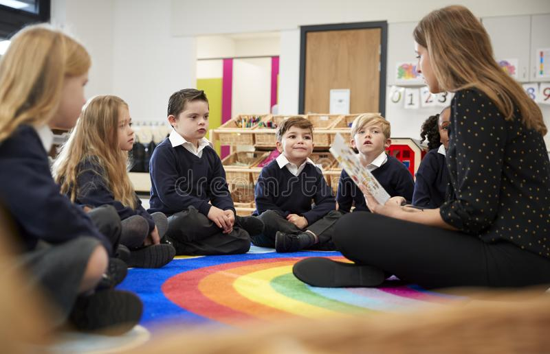 女性主要学校老师坐地板在读书的教室对她的类,选择聚焦 免版税库存照片