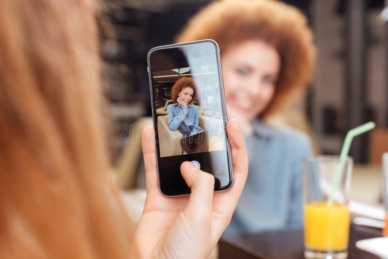 女性举行的智能手机和为照相妇女咖啡馆的 库存图片