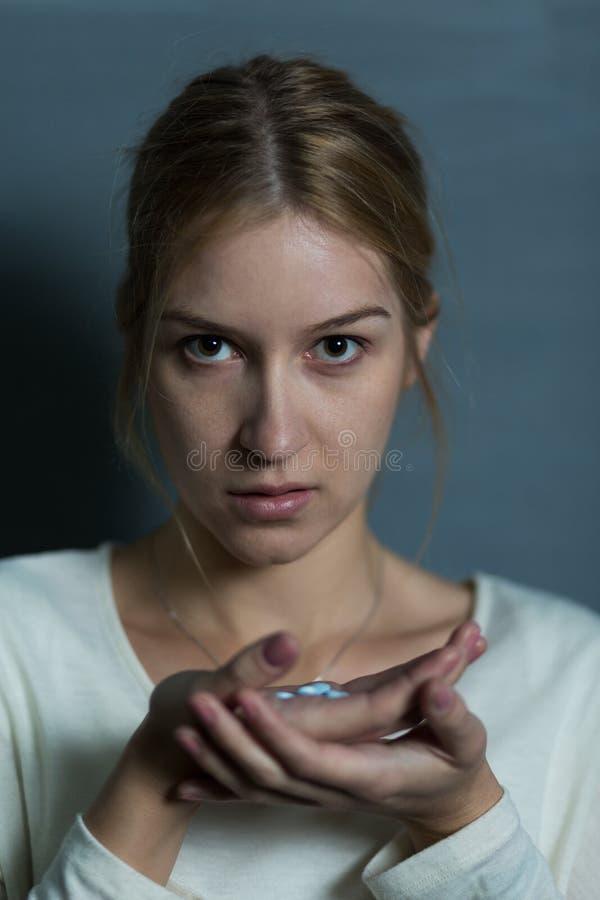 女性举行的极少数药片 免版税库存图片