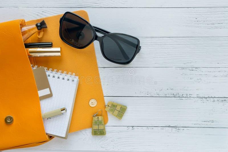 o 女性事、化妆品、sunglass、笔记本和橙色提包在木背景与copyspace ?? 免版税库存图片