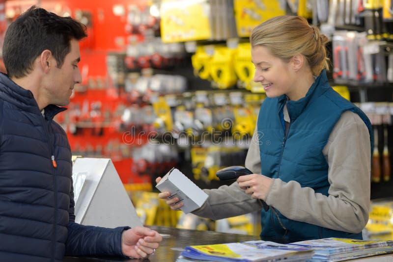 女性五金店卖主扫描客户项目 库存图片