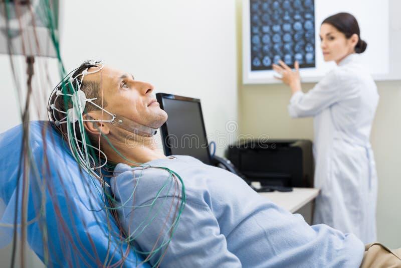 女性人医生执行的脑波记录仪  库存照片