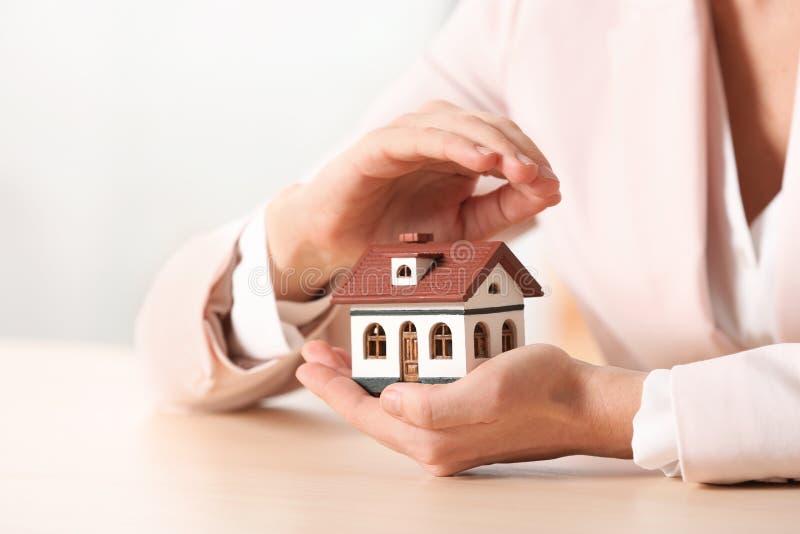 女性代理覆盖物房子模型在桌,特写镜头上 库存照片