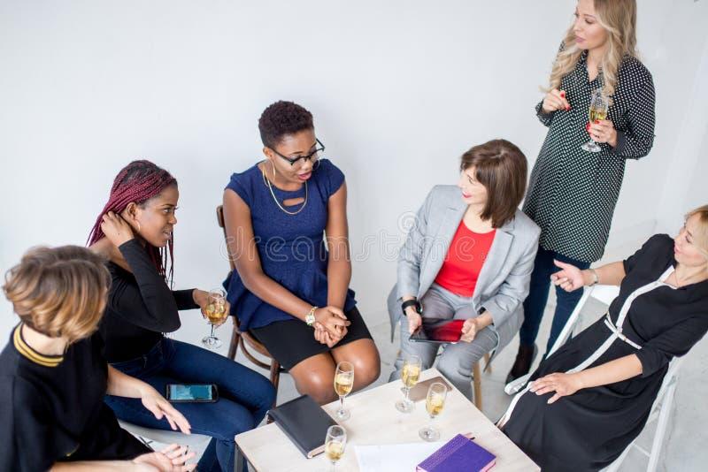 女性企业队画象在有杯的现代演播室香槟 免版税库存照片