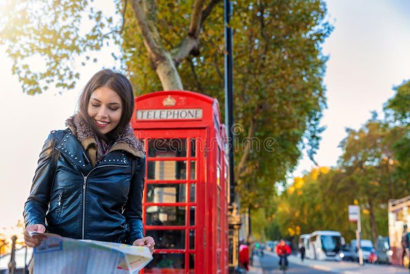 女性伦敦游人看在一个红色电话亭前面的一张地图 免版税库存照片