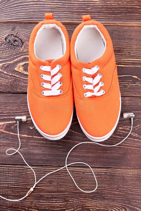 女性体育鞋子和耳机 库存照片