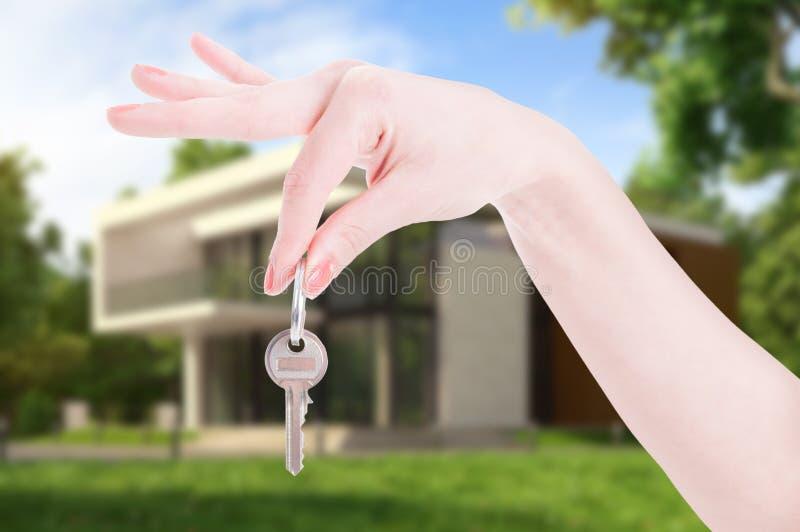 女性作为房地产概念的手垂悬的房子钥匙 免版税库存图片
