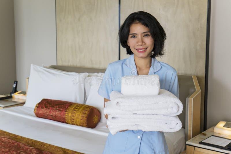 女性佣人在卧室拿着清洁毛巾 库存照片