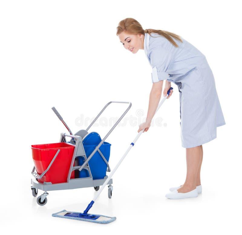 女性佣人清洁地板 免版税库存图片