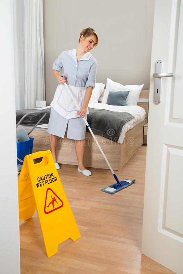 女性佣人清洁地板 库存图片