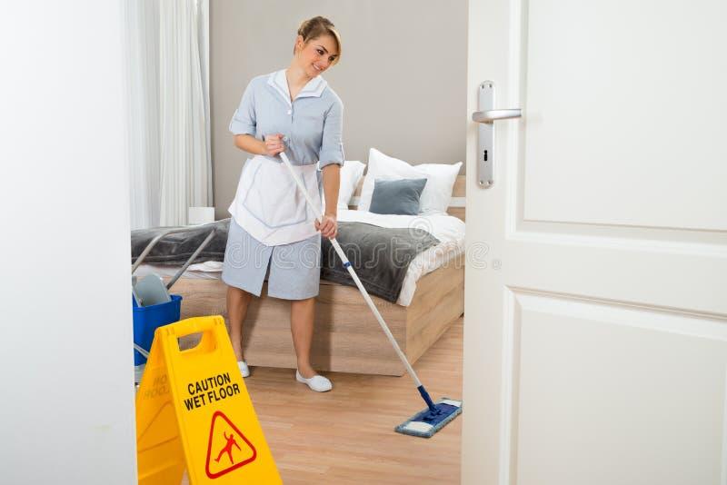女性佣人清洁地板 免版税库存照片