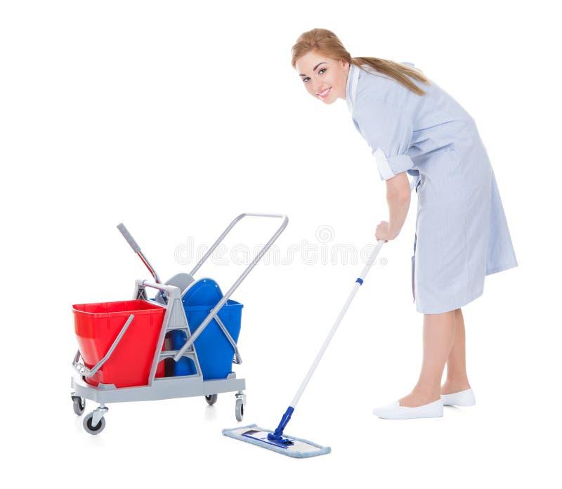 女性佣人清洁地板 免版税图库摄影