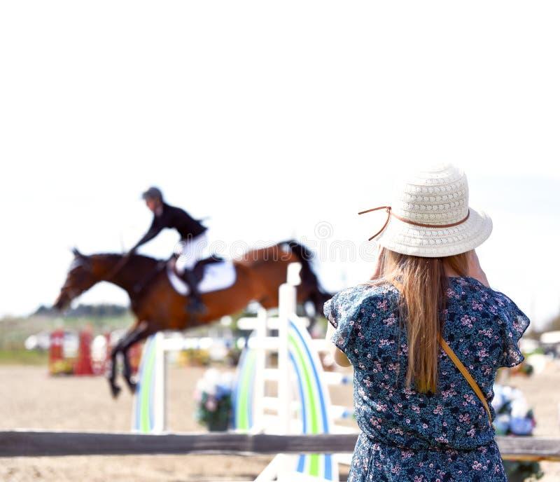 女性佩带的帽子观看的马跳跃的事件 免版税图库摄影