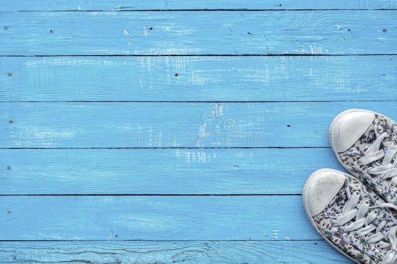 女性佩带蓝色木表面上的对一双运动鞋 免版税库存照片