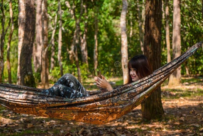 女性使用的智能手机,当休息在野营的活动的吊床在森林里时 免版税库存图片