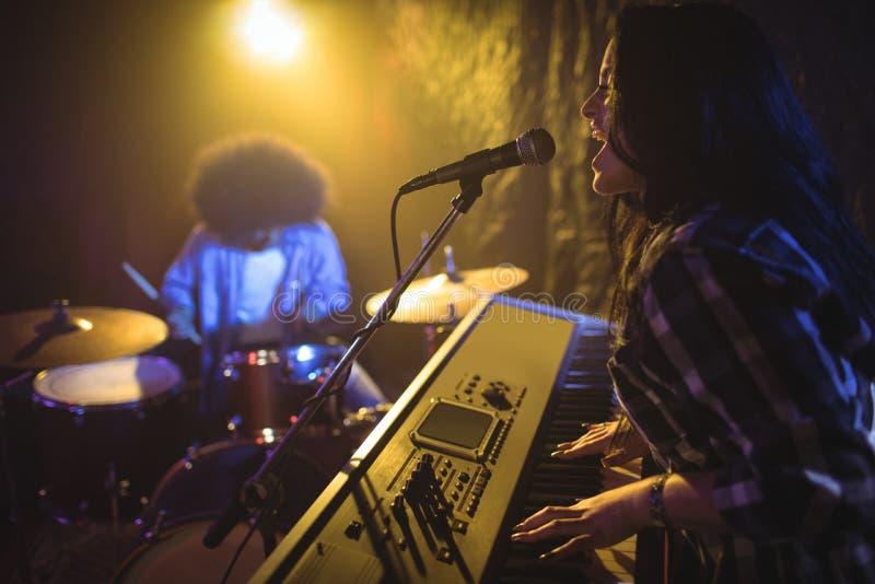 女性使用的钢琴,当执行在夜总会时 免版税图库摄影