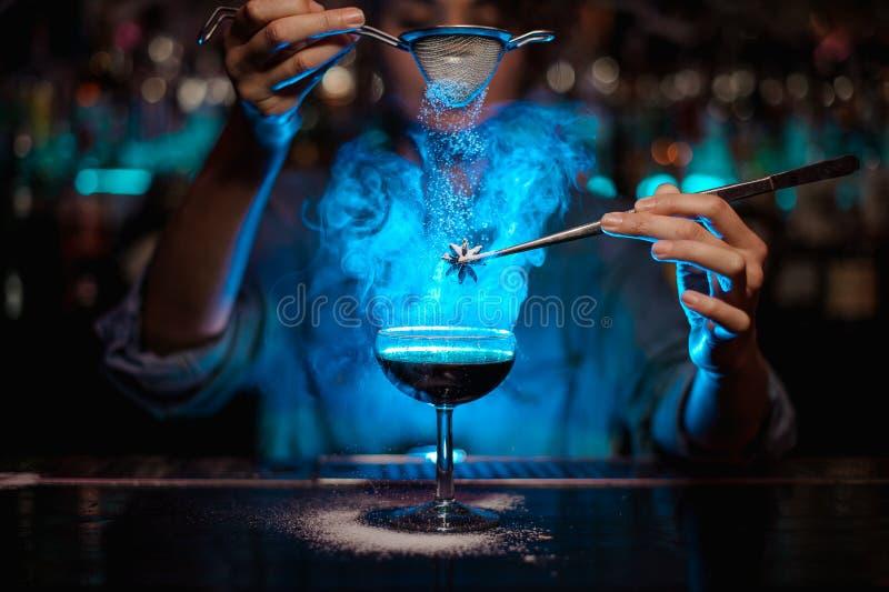 女性侍酒者说到一个棕色鸡尾酒和倒在一发火焰的badian在镊子在蓝色光的糖粉 库存照片