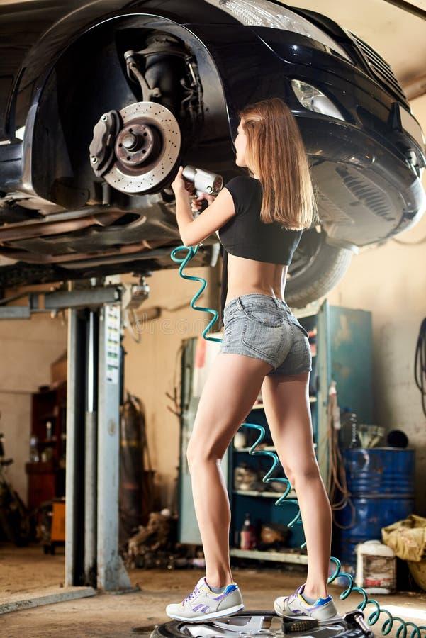 女性修理在车库汽车举的操纵机构 库存照片