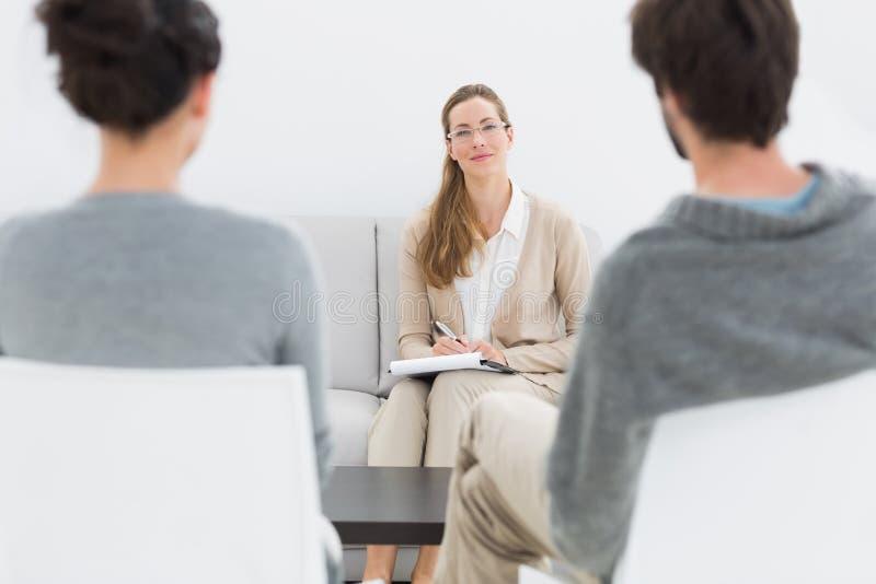 女性关系顾问在与年轻夫妇的会议 库存图片