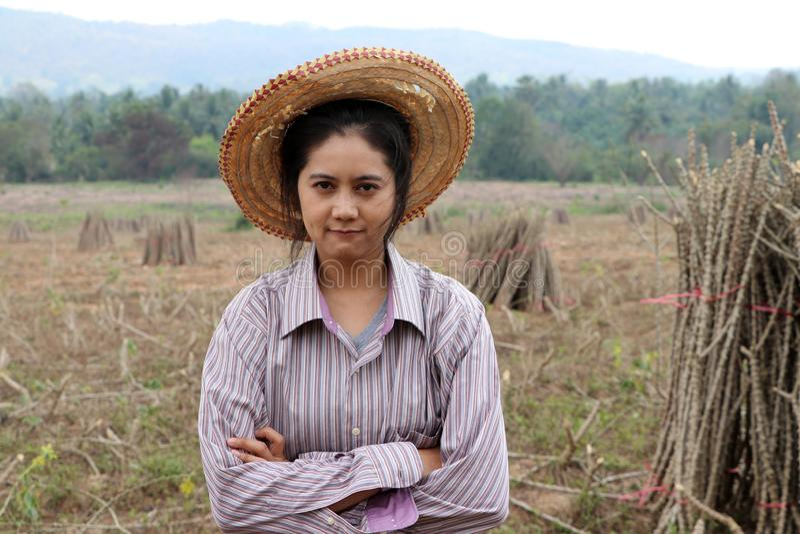 女性农夫身分和拥抱胸口在堆珍珠粉肢体旁边在农场 免版税库存图片