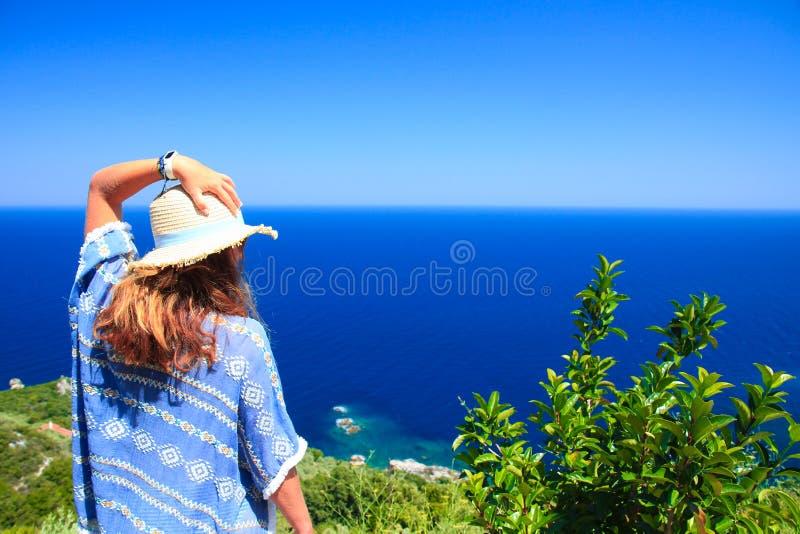 女性凝视从小山的海,当拿着她的有她的左手的时帽子 在白天期间的射击在夏天 库存照片