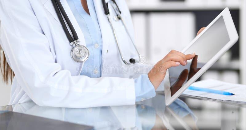 女性医师手特写镜头使用数字片剂的,当坐在玻璃书桌在医院办公室时 的医学 免版税库存照片