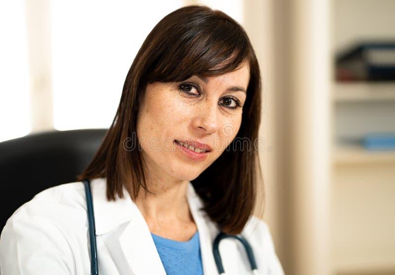 女性医生与听诊器和剪贴板一起使用在有自然面孔表示的医疗办公室 图库摄影