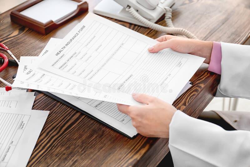 女性医生与文件一起使用在办公室 库存图片
