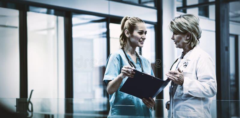 女性医生和护士谈论在一个医疗报告 免版税库存照片