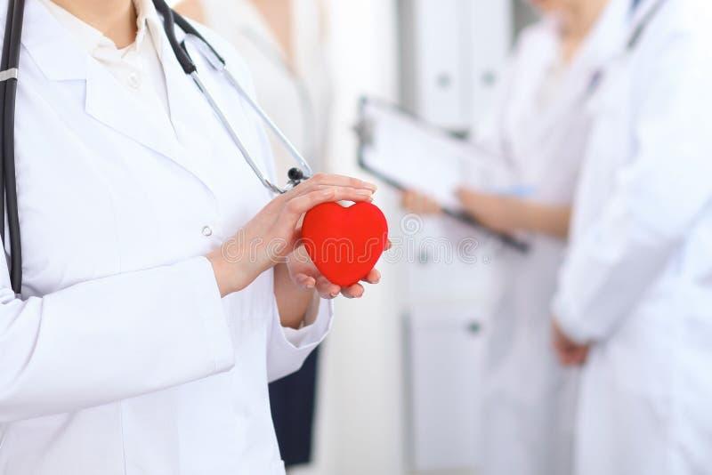 女性医生在她的手上的拿着心脏 坐在背景中的医生和患者 在的医学的心脏病学 库存照片