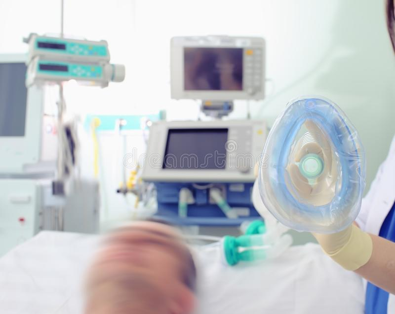 女性医生在手套的手上的拿着氧气面罩在Th旁边 免版税库存照片