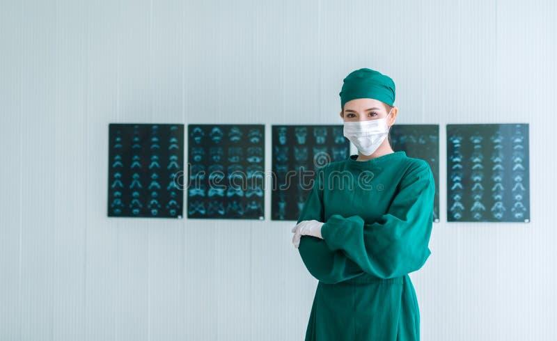女性医生外科医生画象以绿色洗刷投入在外科手套和看照相机 年轻亚裔医生妇女与 库存照片