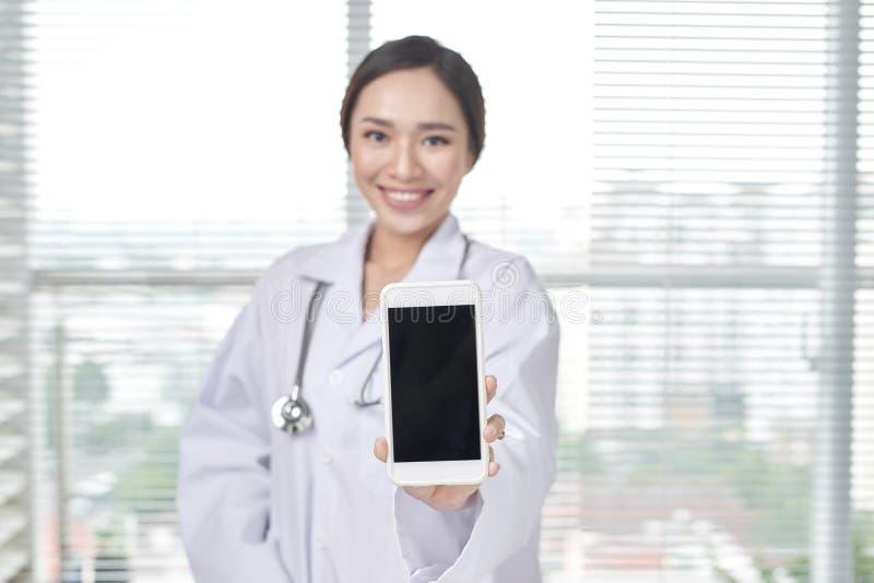 女性医生显示智能手机黑屏  免版税库存图片
