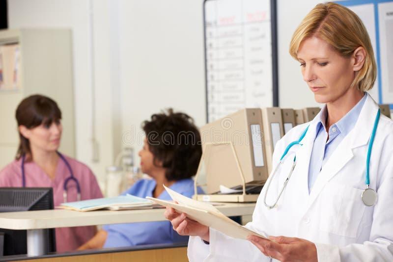 女性医生Reading Patient Notes At护理岗位 库存图片