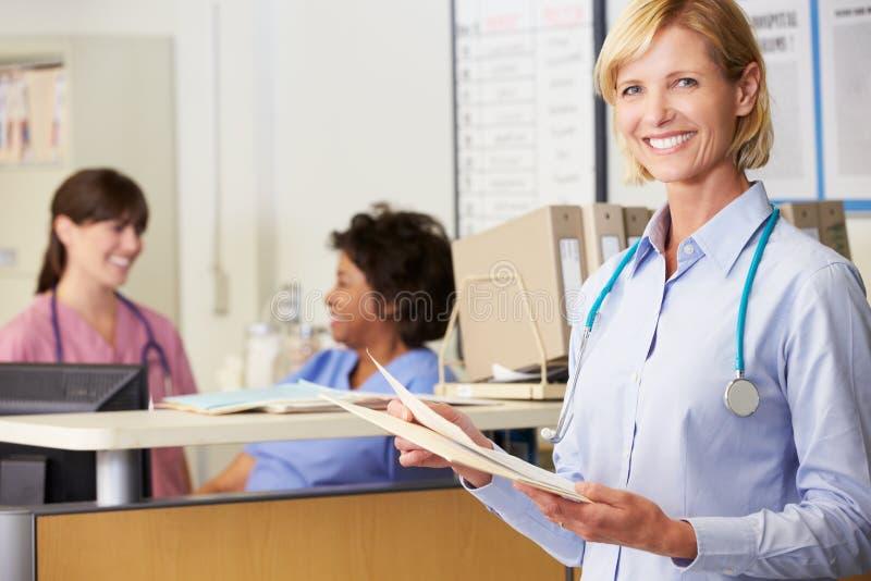 女性医生Reading Patient Notes At护理岗位 免版税库存照片