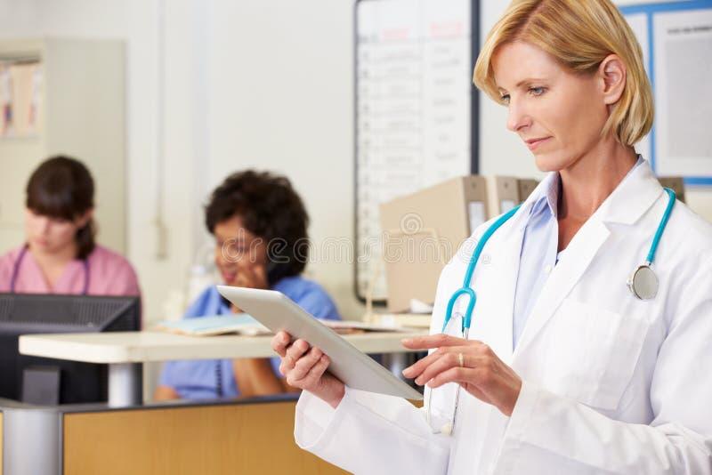 女性医生Using Digital Tablet At护理岗位 库存照片