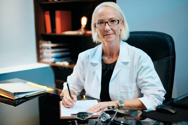 女性医生Working In Hospital微笑对照相机的Office画象  图库摄影