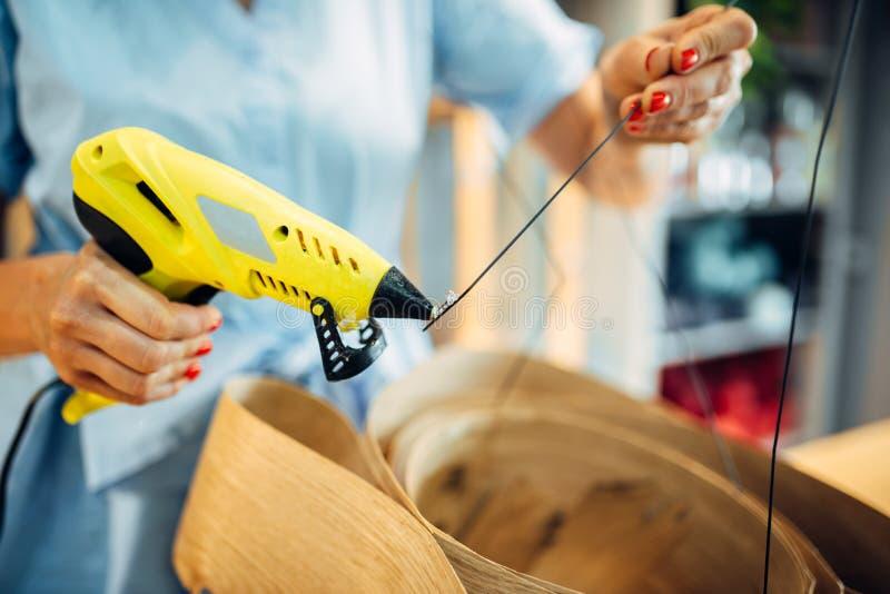 女性卖花人与在花店的胶水枪一起使用 库存照片