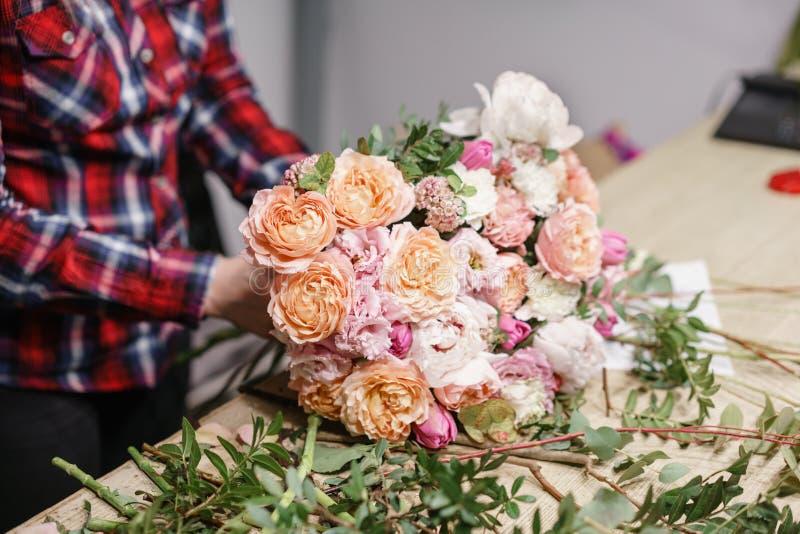 女性卖花人花卉车间-做美好的花构成花束的妇女 Floristry概念 免版税库存照片
