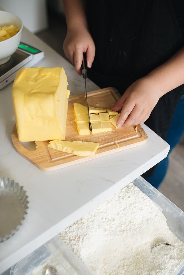 女性厨师切口黄油的播种的图象在厨房里 图库摄影