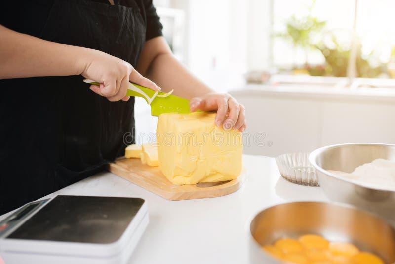 女性厨师切口黄油的播种的图象在厨房里 库存照片