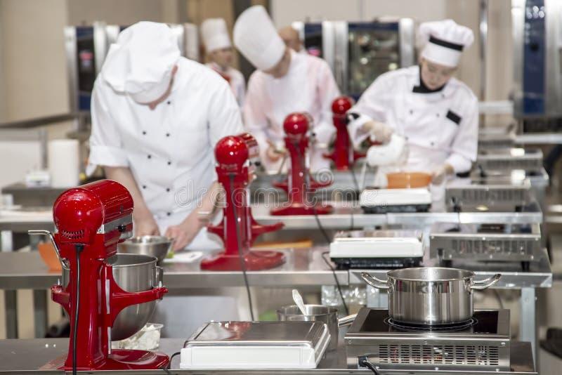女性厨师在旅馆或餐馆的厨房里准备酥皮点心 免版税库存图片