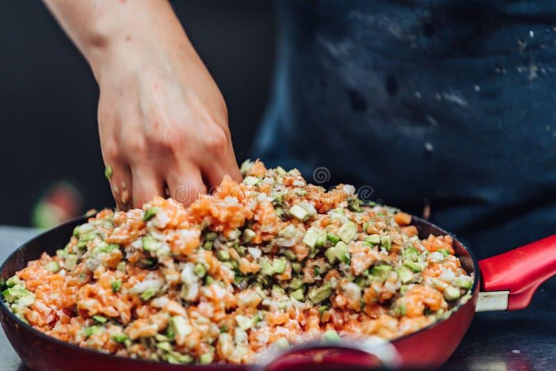 女性厨师混合的三文鱼用在碗的鲕梨-行动用可看见仅的手 库存照片