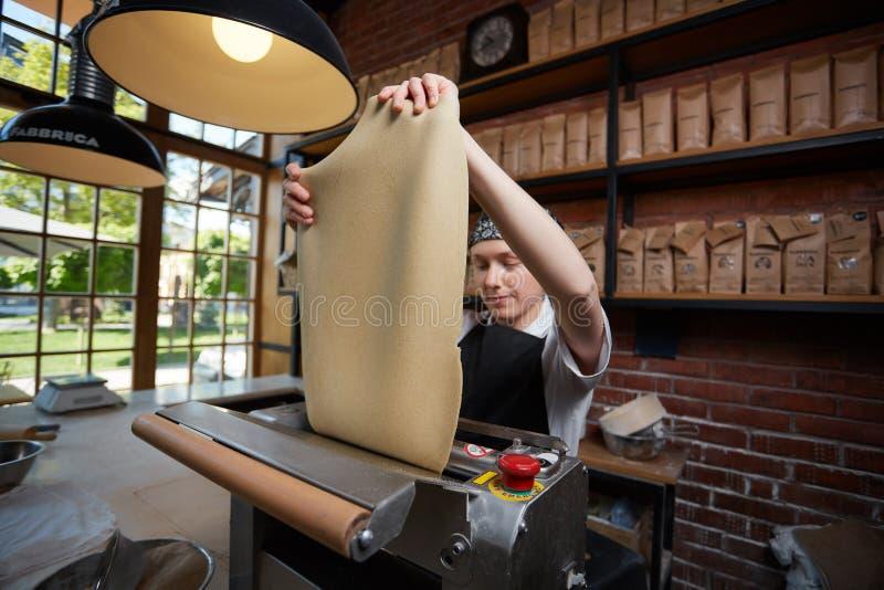 女性厨师辗压面团 免版税库存照片