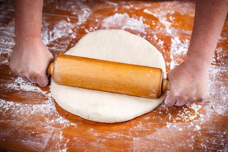 女性厨师铺开的面团 免版税库存照片