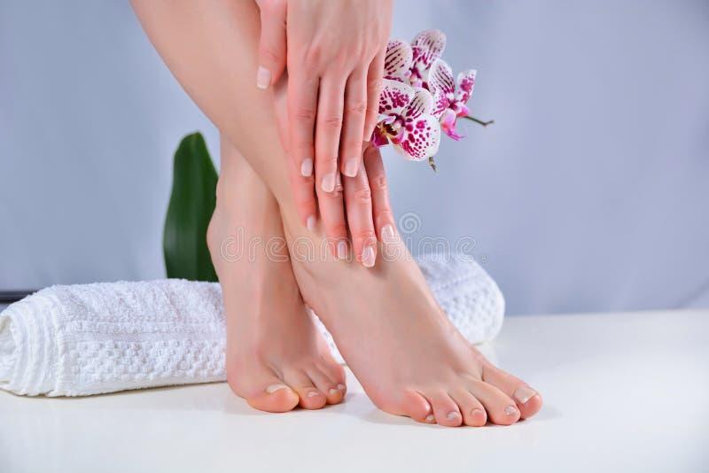 女性双脚和双手,在毛巾上做天然光滑的彩色修指甲和修脚 免版税库存照片