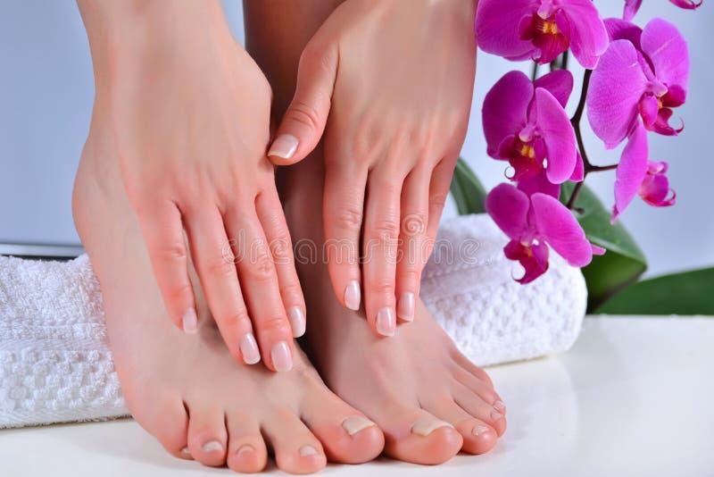 女性双脚和双手,用毛巾上的天然光亮色美甲和足疗 图库摄影