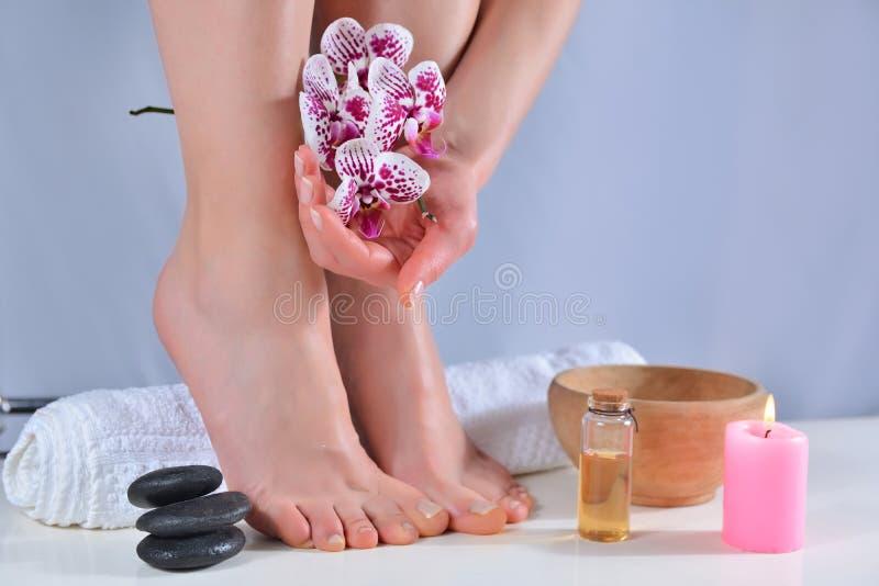 女性双脚和双手,用毛巾上的天然光亮色美甲和足疗 库存照片