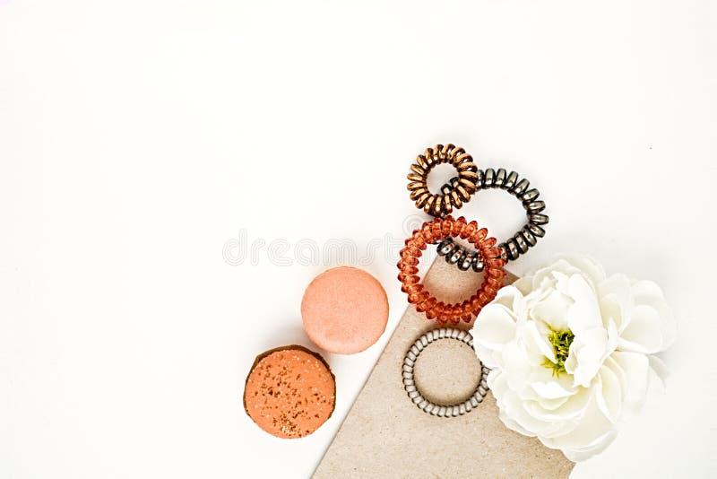 女性发带、macarons和花平的位置在白色 库存照片
