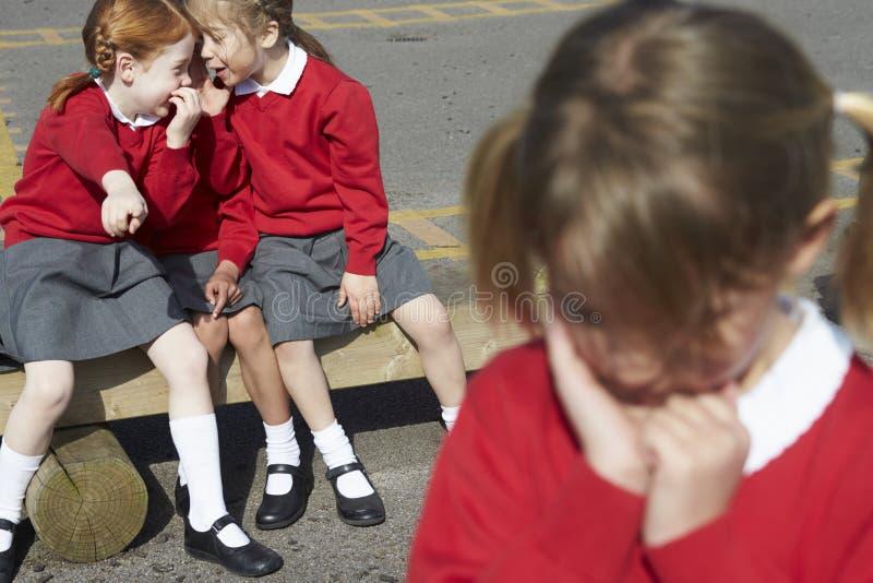 女性台中国小学生耳语在操场 免版税库存照片